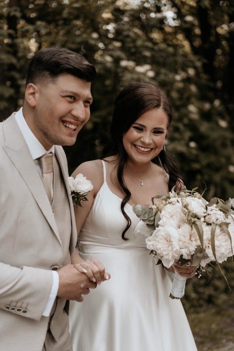 Fotoshooting Brautpaar Jana und Emre 2019, sie trägt ein wunderschönes weißes Brautkleid und er einen creme farbenen Smoking. Beide lachen auf dem Bild.