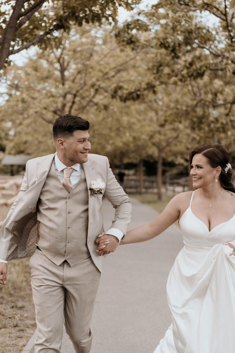 Das Brautpaar Jana und Emre läuft Hand in einen Weg entlang und schaut sich verliebt an
