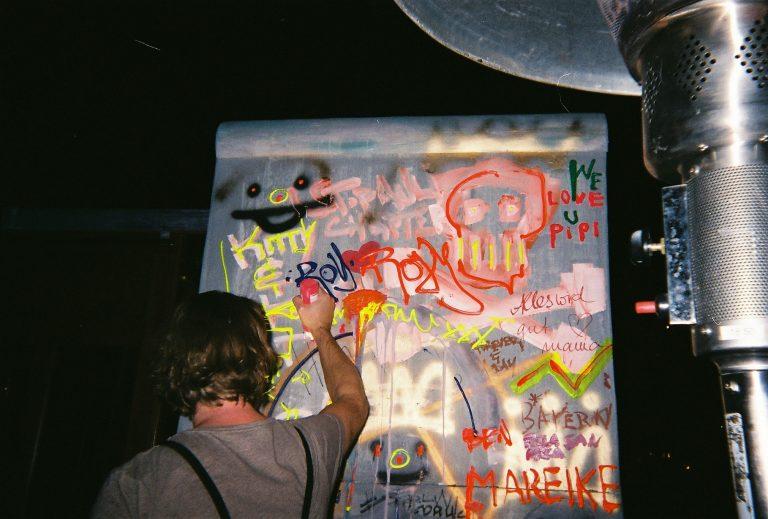 Hochzeitsgast vor einem besprühten Erinnerungsstück der Berliner Mauer in Originalgröße.