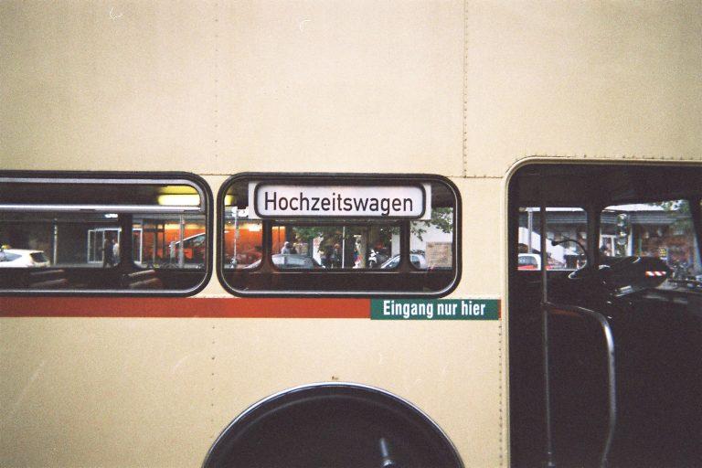 Eine Nahaufnahme des Doppeldecker Buses der als Hochzeitswagen gekennzeichnet ist und die Gäste des Brautpaars shuttelt von A nach B