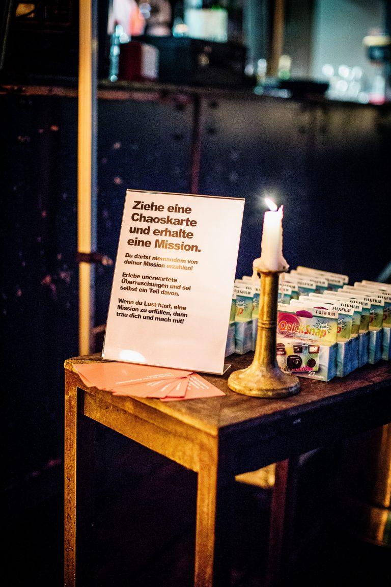 Aufsteller mit Anleitung Chaoskarte und Quick Snap einmal Kameras stehen mit einer Kerze auf einem Tischlein am Polterabend von Laura und Philipp 2019 in Berlin.