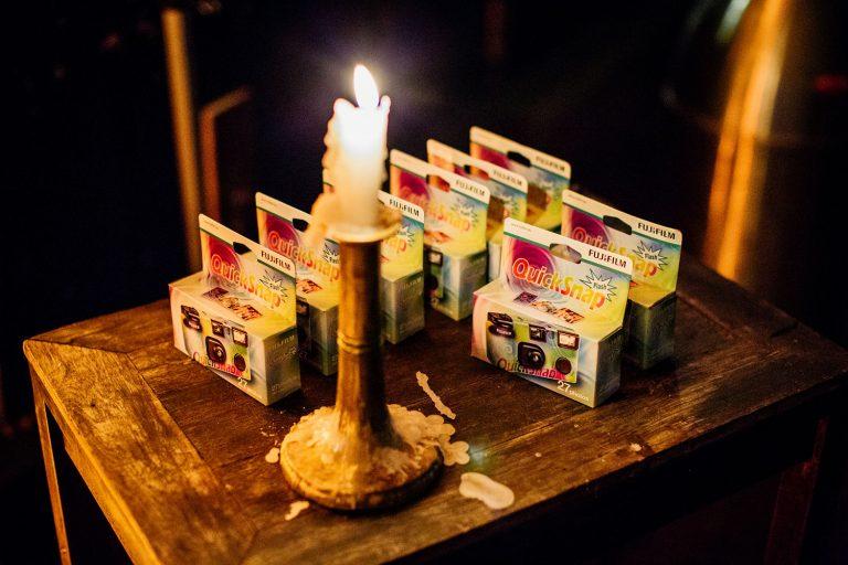 Quick Snap einmal Kameras stehen mit einer Kerze auf einem Tischlein am Polterabend von Laura und Philipp 2019 in Berlin.
