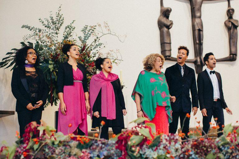 Gospelchor mit sechs Chorsängern die singen in der Kirche zu Beginn der kirchlichen Trauung von Laura und Philipp 2019