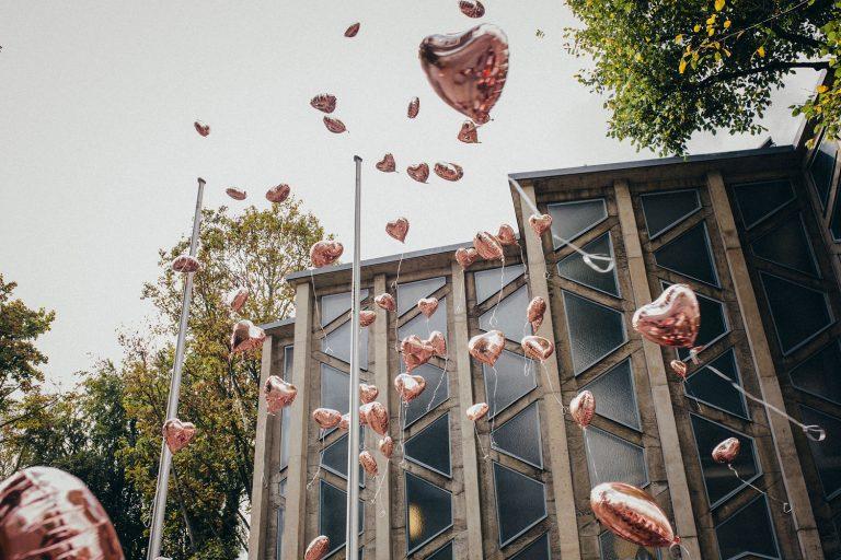 Herzförmige glänzende Heliumballons fliegen vor der Kirche nach der kirchlichen Hochzeit von Laura und Philipp 2019 in die Luft
