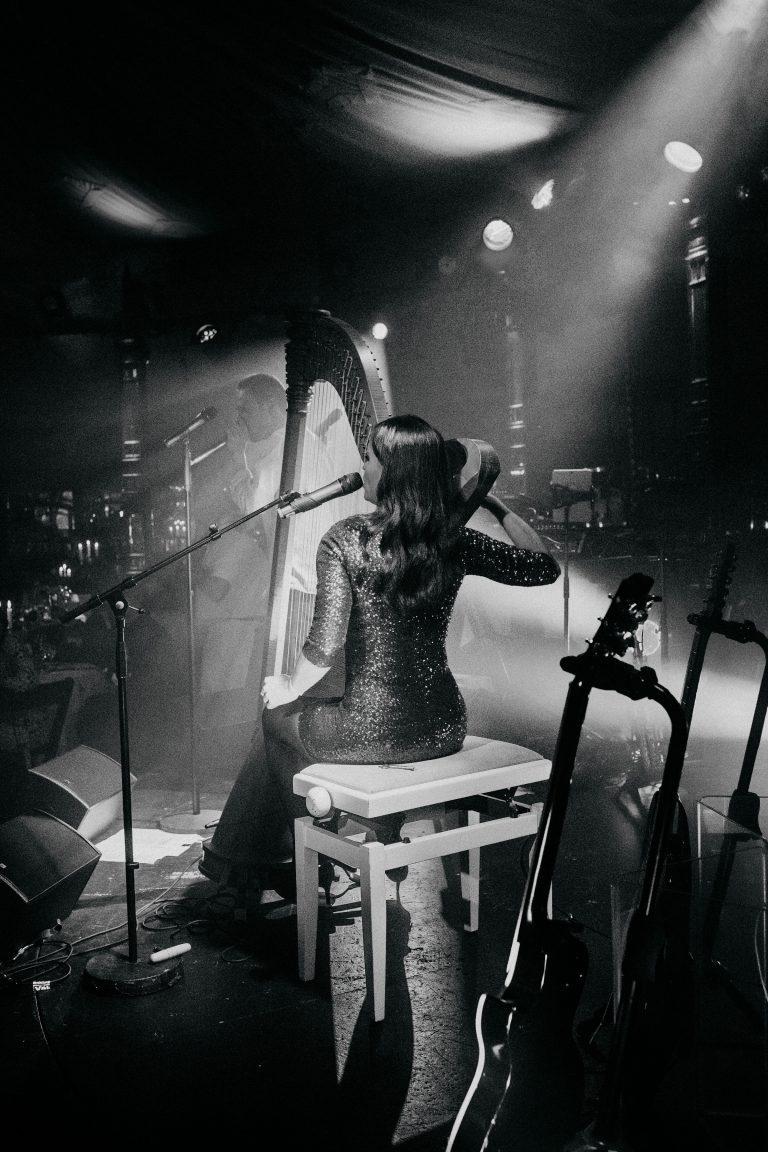 Bild einer Harfe Spielerin Rückansicht in schwarz weiss auf der Hochzeitslocation am Abend der Hochzeit von Laura und Philipp 2019.